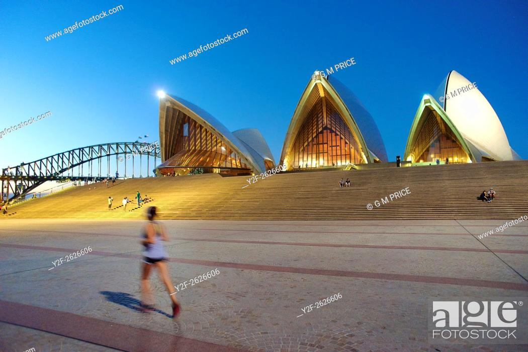 Stock Photo: jogger and Sydney Opera House at dusk, with Harbour Bridge in the background.