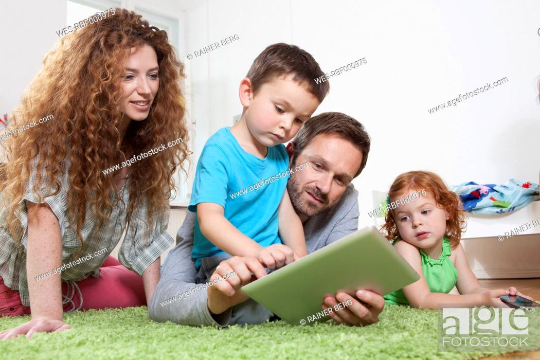 Stock Photo: Germany, Berlin, Father using digital tablet with family on floor.