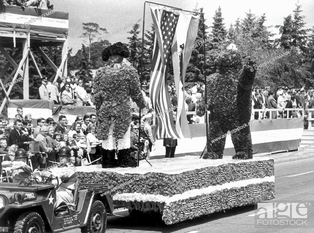 Stock Photo: A show car with the Berlin Bear and a US soldier of the independence war made of flowers and plants driving past a VIP stand during a parade on occasion of the.