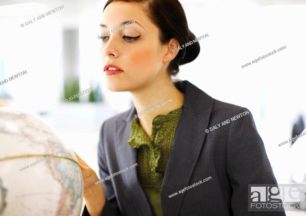Stock Photo: Businesswoman looking at globe.