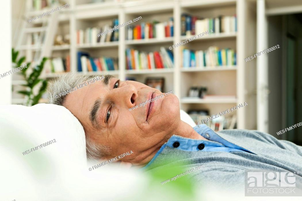 Stock Photo: Germany, Berlin, Senior man on couch, portrait.