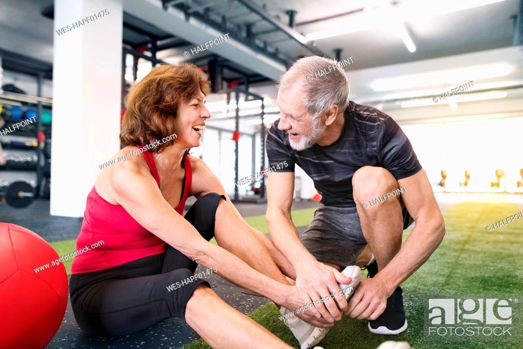 Stock Photo: Happy senior couple exercising in gym.