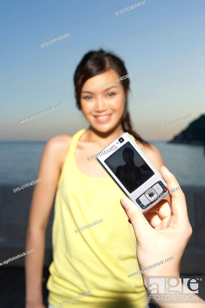 Stock Photo: Man taking picture with mobile phone of Young Lady.