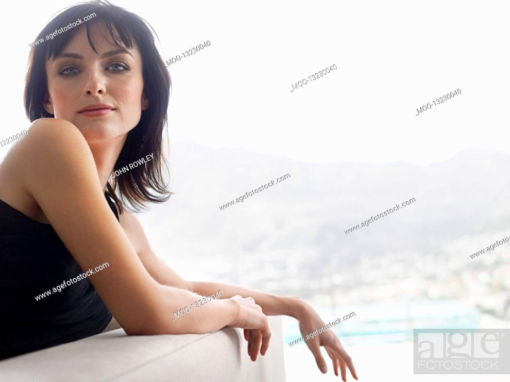 Stock Photo: Young woman leaning on couch indoors.