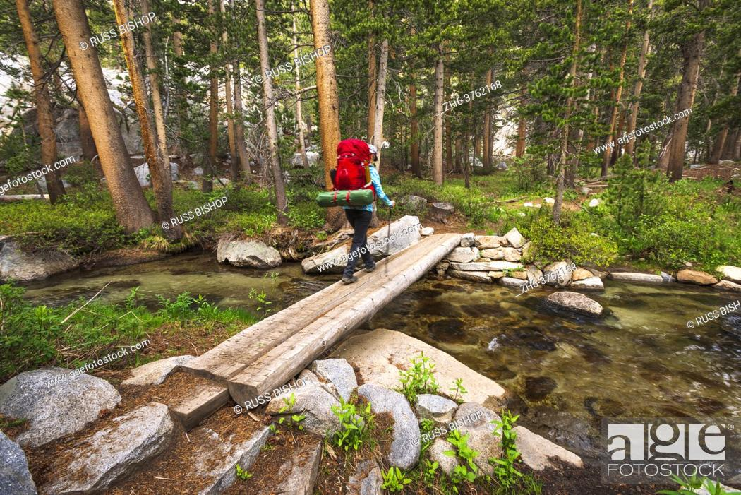 Stock Photo: Backpacker crossing creek in the John Muir Wilderness, Sierra Nevada Mountains, California USA.