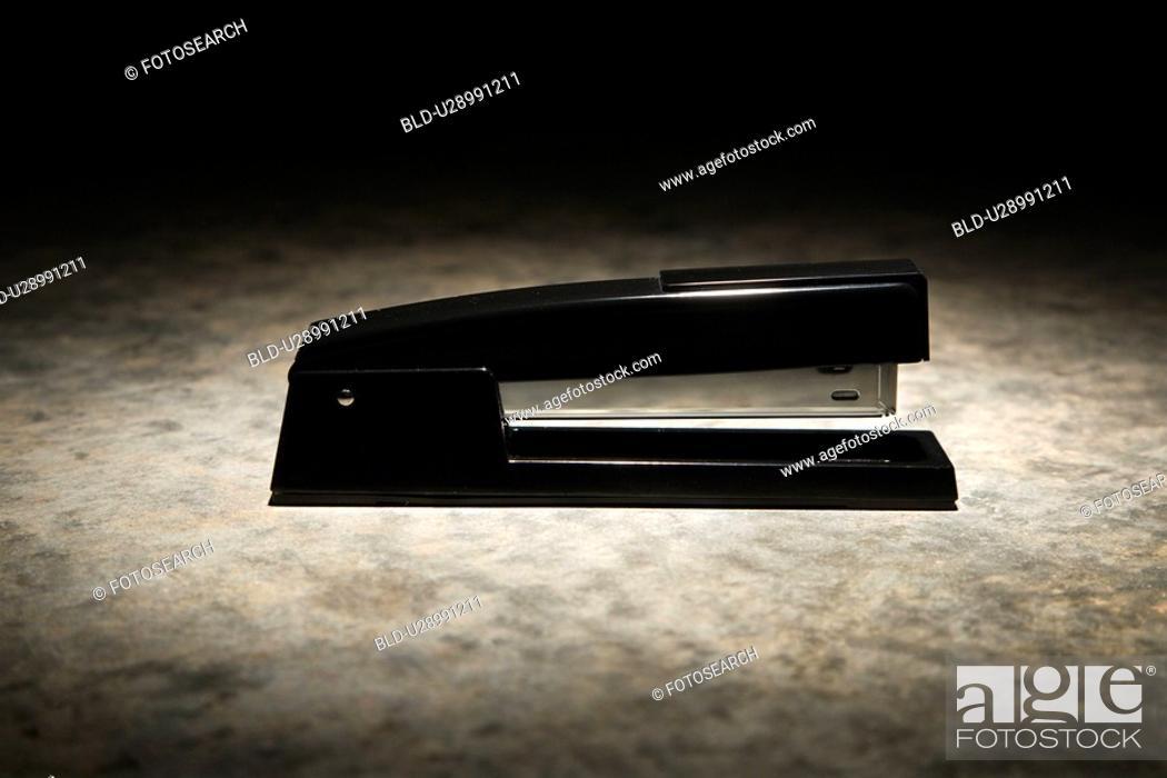 Stock Photo: Black stapler with black vignette.