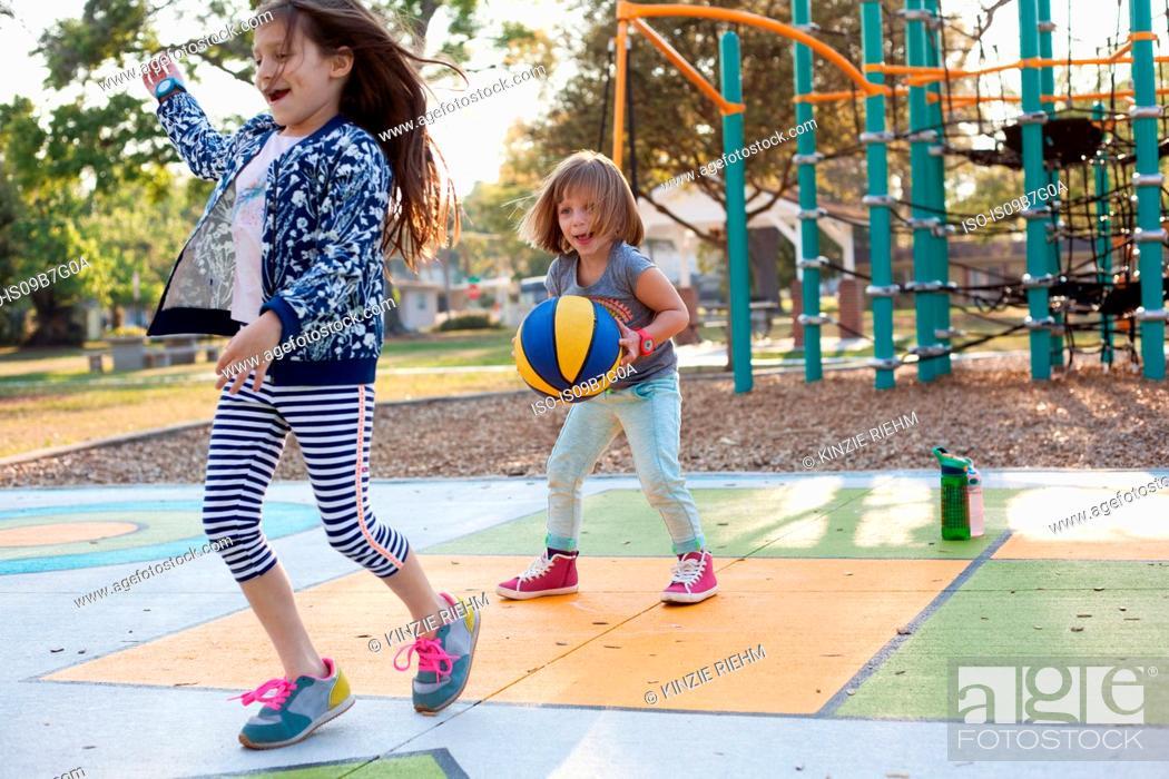 Stock Photo: Children playing basketball in playground.