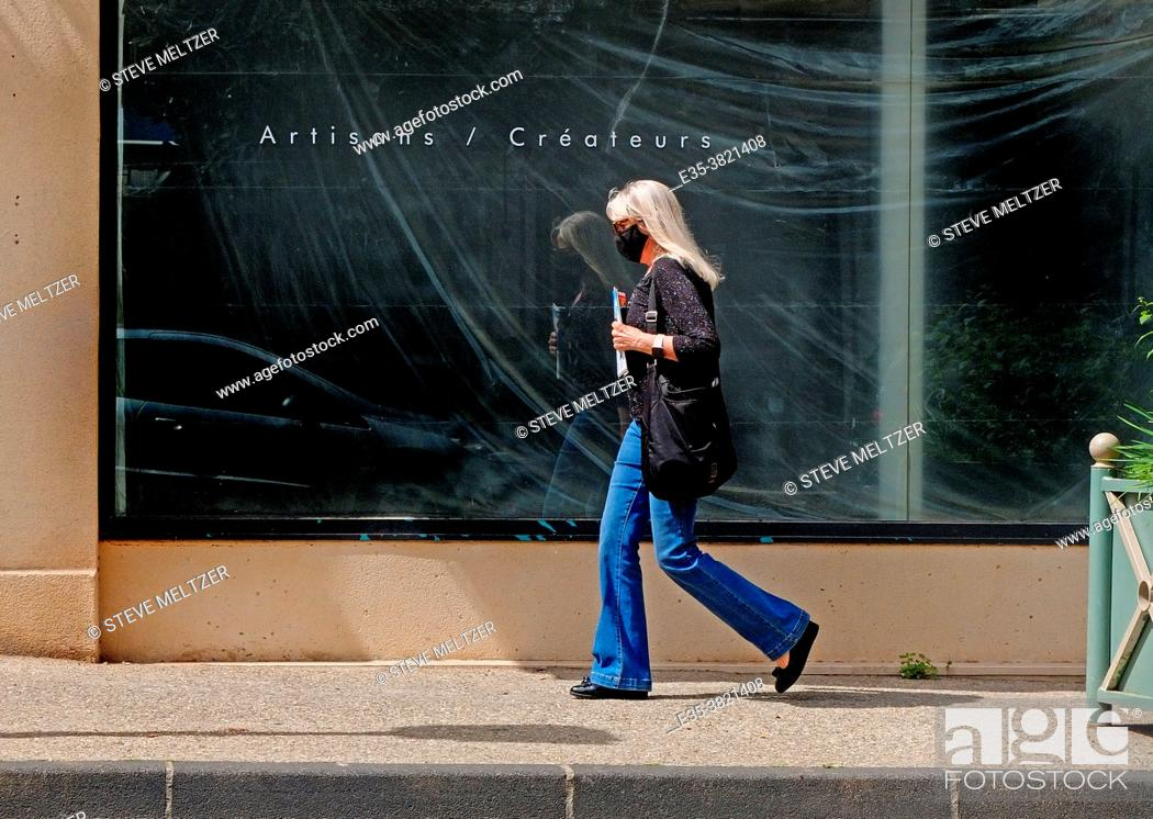 Stock Photo: During the 2021 confinement a woman strides past an empty shop.