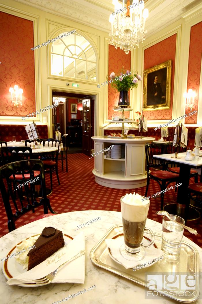 Stock Photo: A slice of Original Sacher- Torte cake with whipped cream, and hot Einspanner black coffee in a typical Einspanner glass  The Elisabeth Salon, Hotel Sacher.