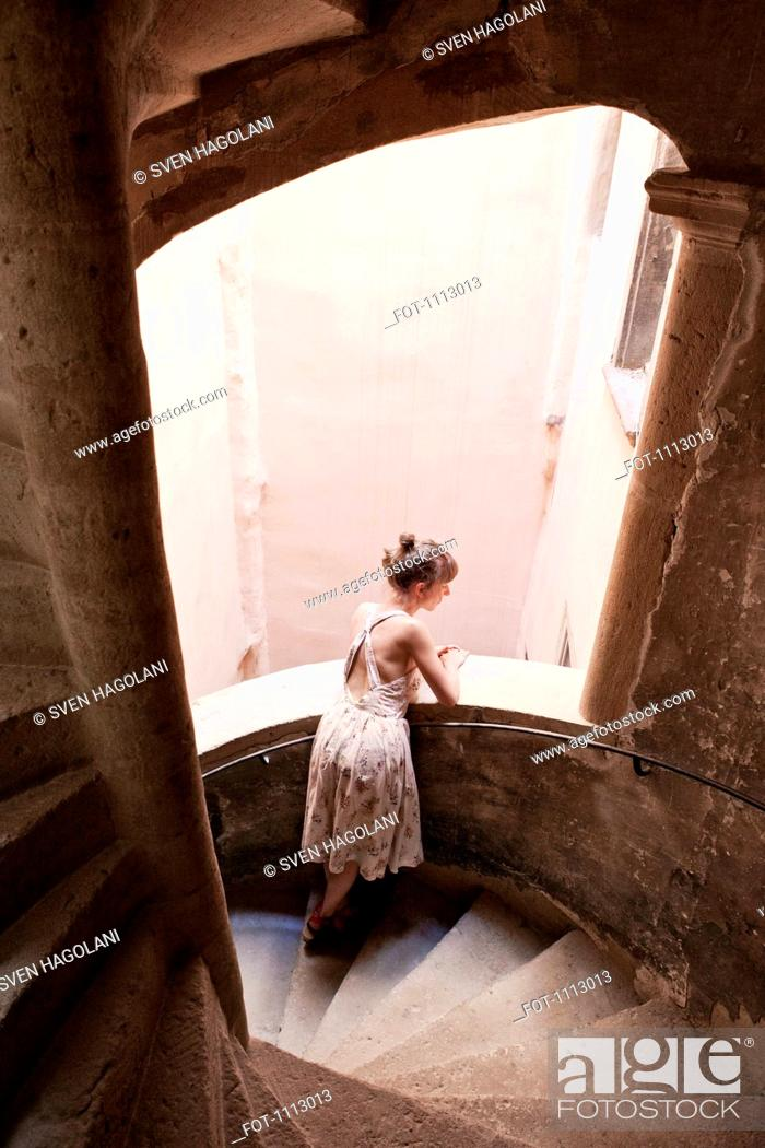 Stock Photo: A woman leaning on a staircase railing and looking outside.