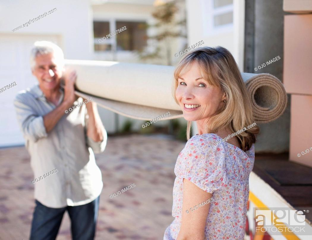 Stock Photo: Couple carrying carpet from moving van.