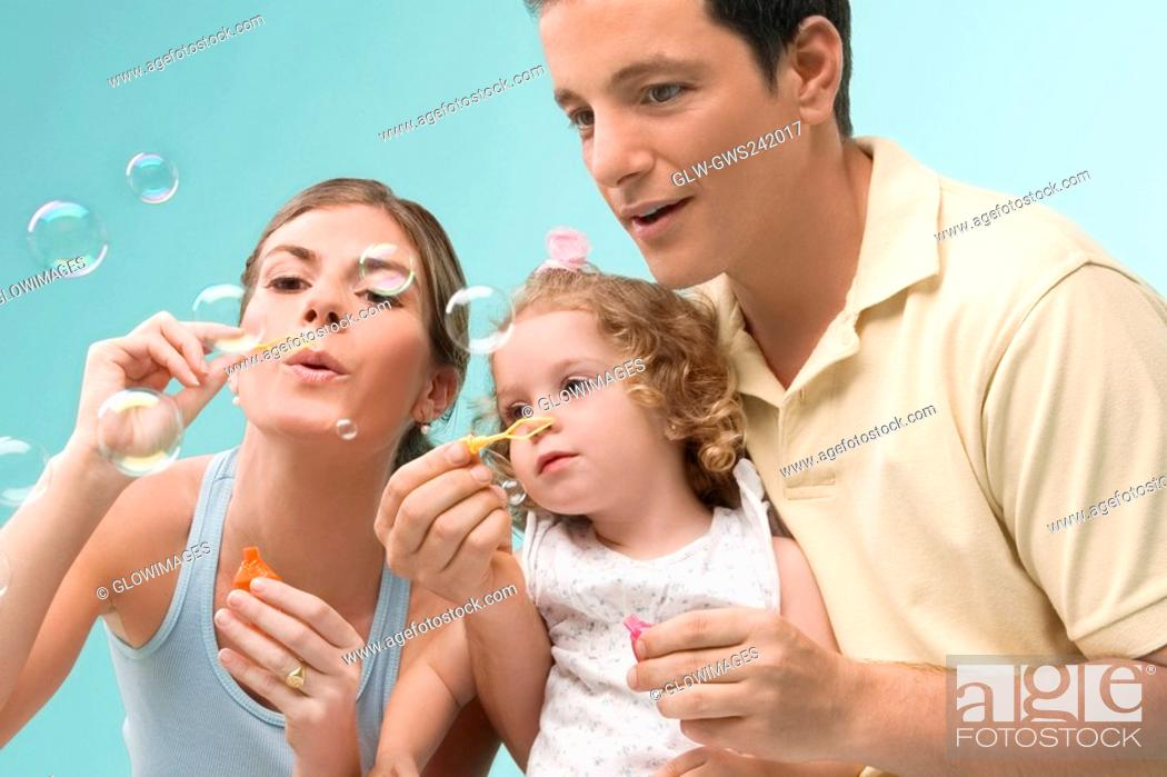 Stock Photo: Mid adult couple blowing bubbles with their daughter.
