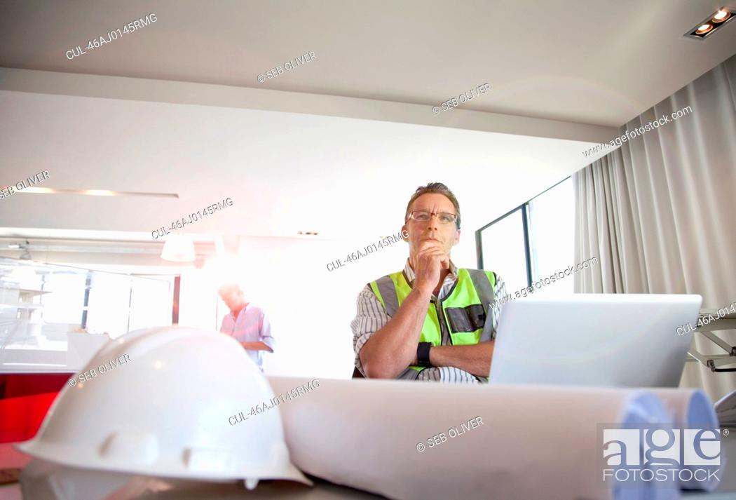 Stock Photo: Construction worker using laptop at desk.