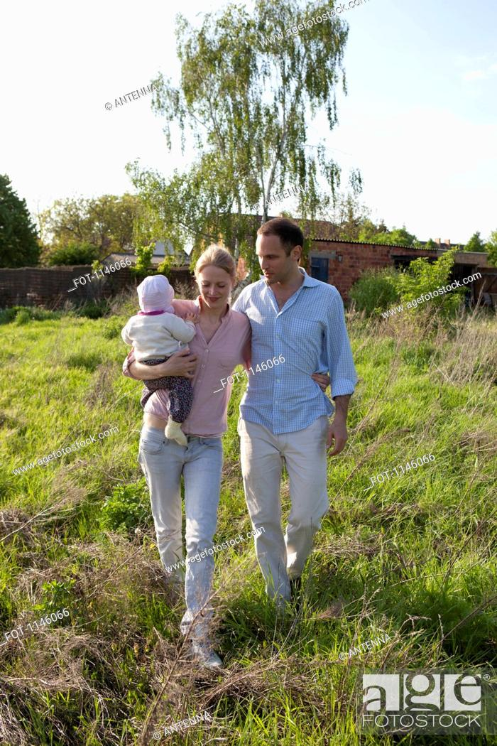 Stock Photo: A man and a woman holding a baby walking in back of their country house.