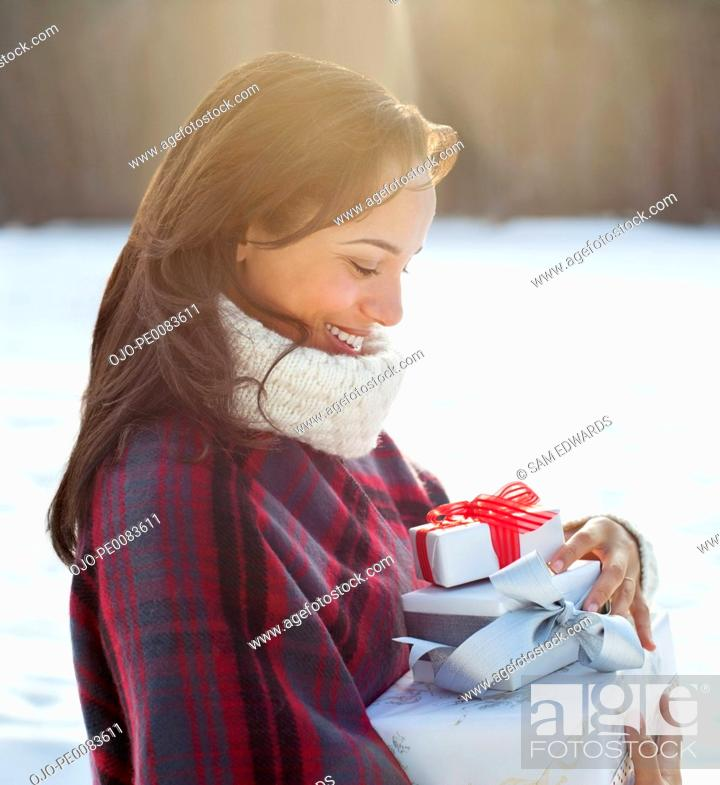 Stock Photo: Smiling woman carrying Christmas gifts.