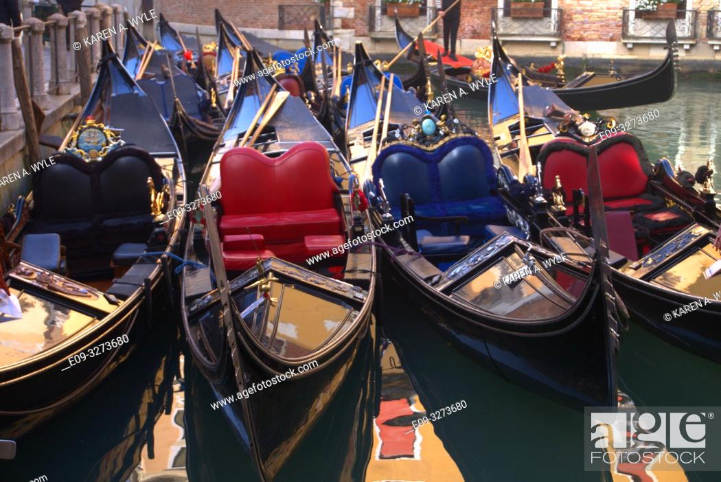 Stock Photo: crowded parking area for gondolas, reflections in water between them, Venice, Italy.