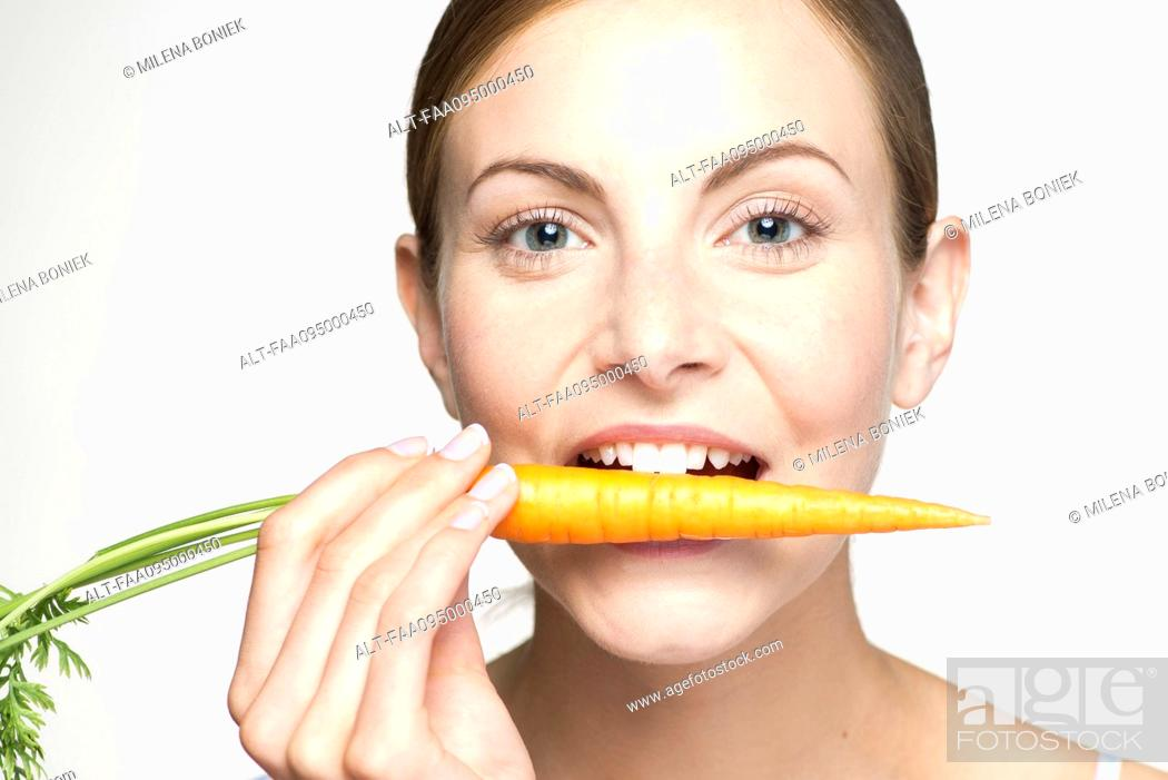 Stock Photo: Young woman biting into carrot, portrait.