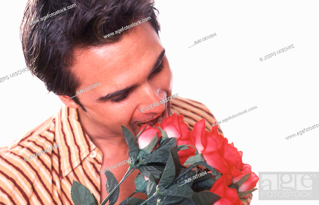 Stock Photo: Portrait of a young man, 20-25 25-30 30-35 years old, dark-haired, masculine and beautiful, with a bouquet of red roses.