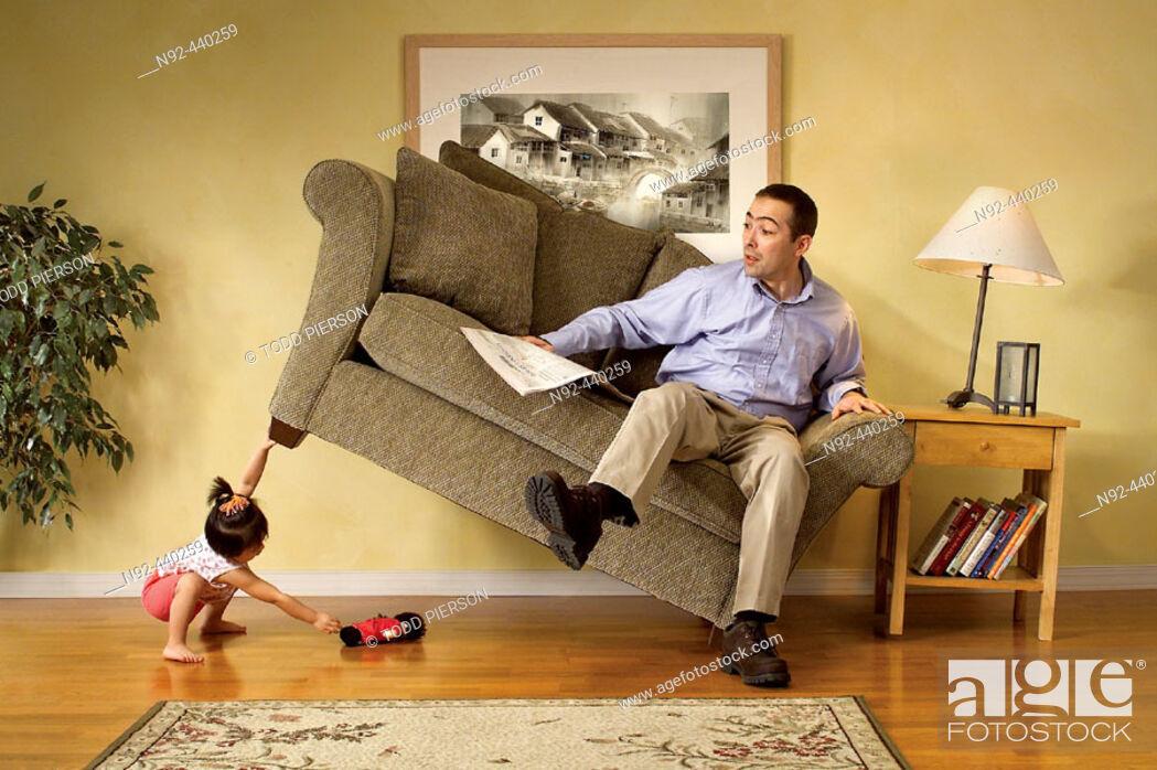 Stock Photo: Girl lifting sofa.