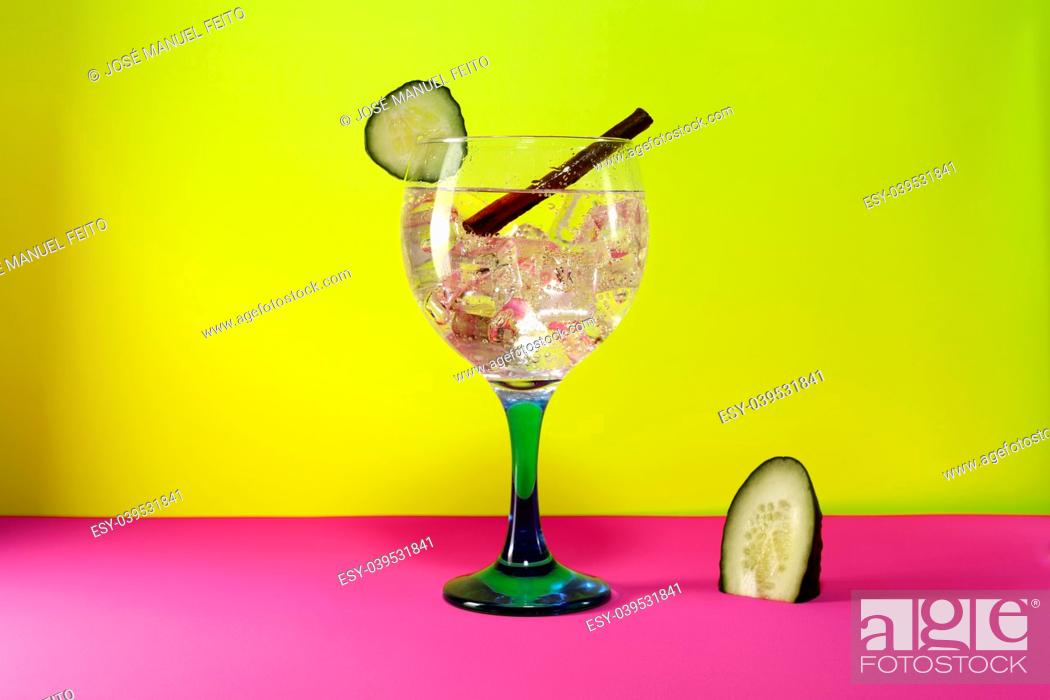 Stock Photo: gin tonic with lemon slice, cinnamon stick and lemon segment on pink and yellow background.