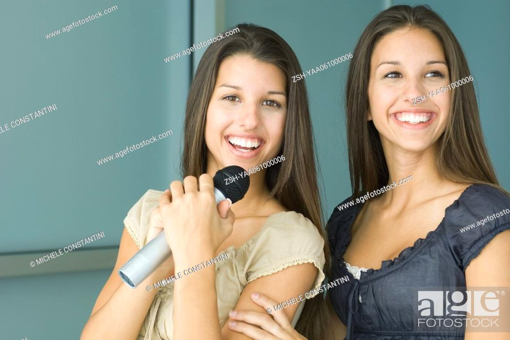 Stock Photo: Teenage twin sisters side by side, both smiling, one holding microphone.
