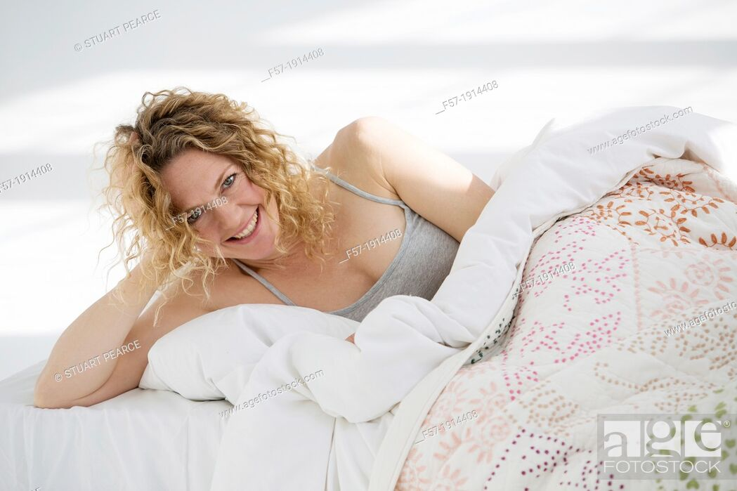 Stock Photo: Attractive young woman waking up in her bed.