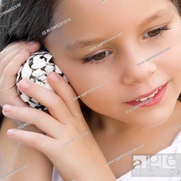 Stock Photo: Close-up of a girl listening to shell.