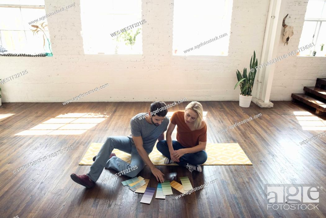 Stock Photo: Young couple sitting on carpet in a loft looking at color samples.