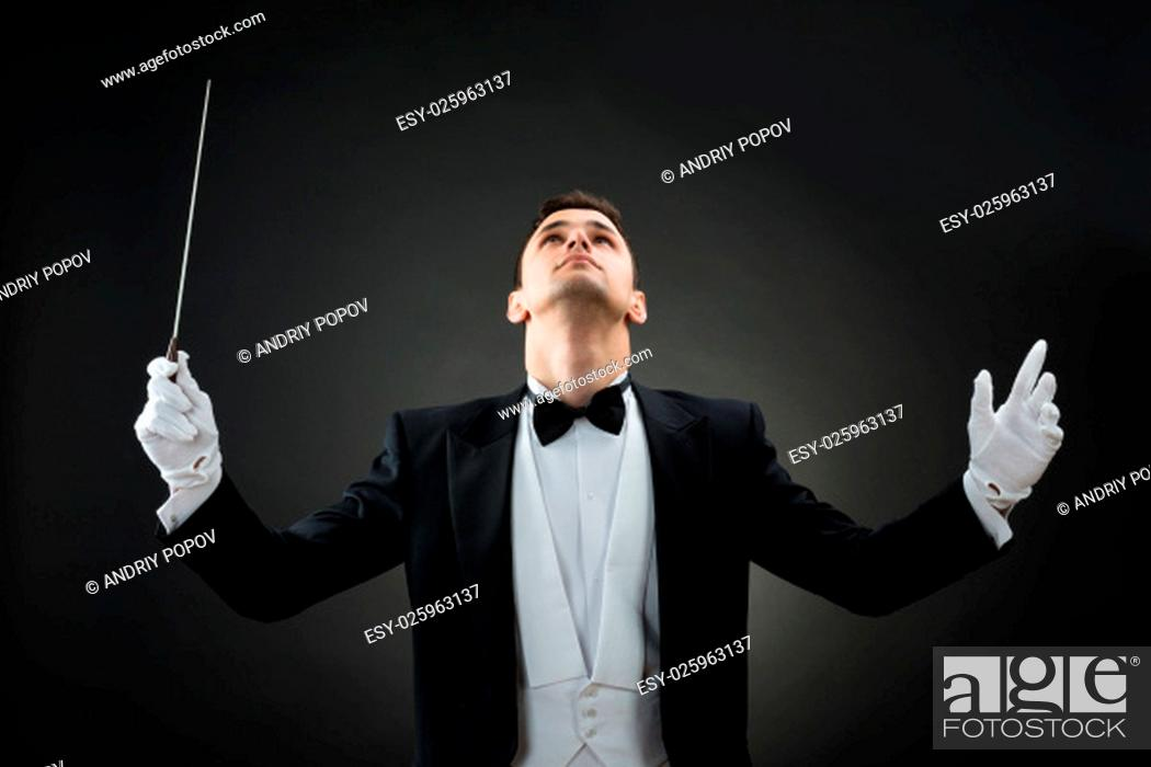 Stock Photo: Young male music conductor looking up while holding baton against gray background.