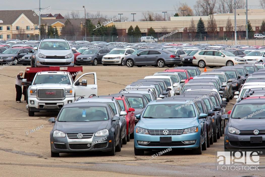 Stock Photo: Pontiac, Michigan - A worker unloads some of the thousands of Volkswagen diesel vehicles that are parked at the vacant Pontiac Silverdome.