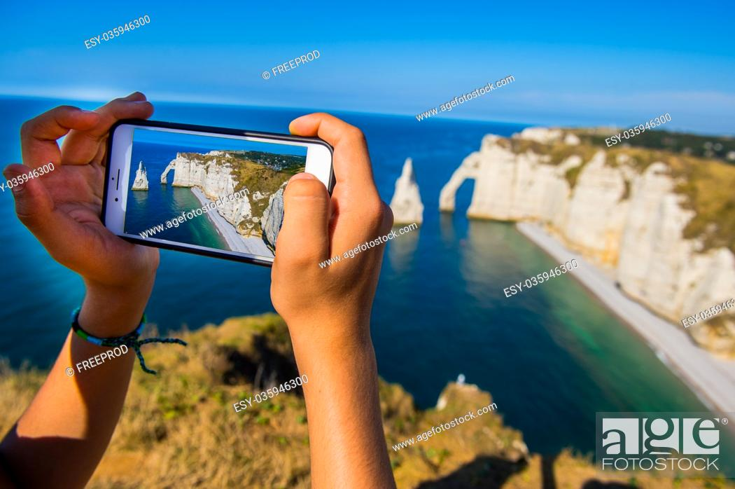 Stock Photo: Smartphone in hand photographing, Chalk cliffs Cote d'Albatre. Etretat Normandie France, Europe.