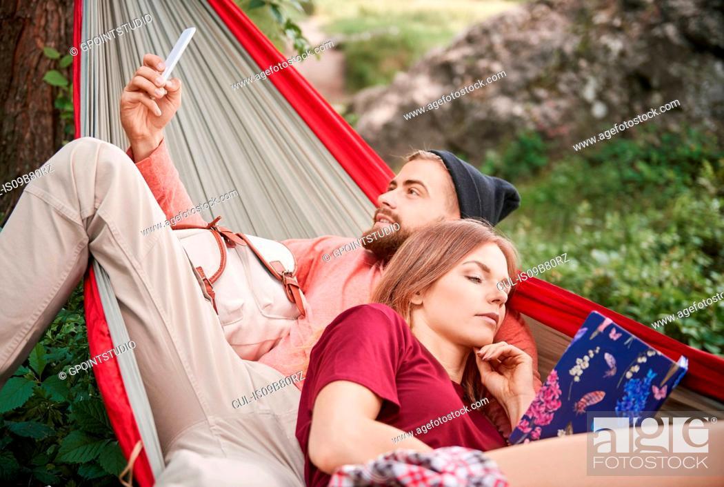 Stock Photo: Couple relaxing in hammock, Krakow, Malopolskie, Poland, Europe.