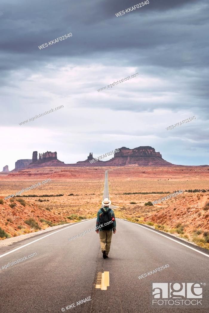 Stock Photo: USA, Utah, Man with backpack walking on road to Monument Valley.