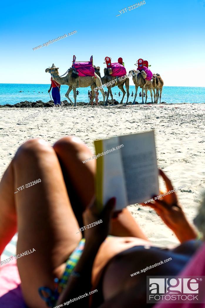 Stock Photo: Africa, North Africa, Maghreb. Governorat of Medenine. Djerba island. Beach of Sidi Mehrez. Tourist riding a book on a beach of Sidi Mehrez.