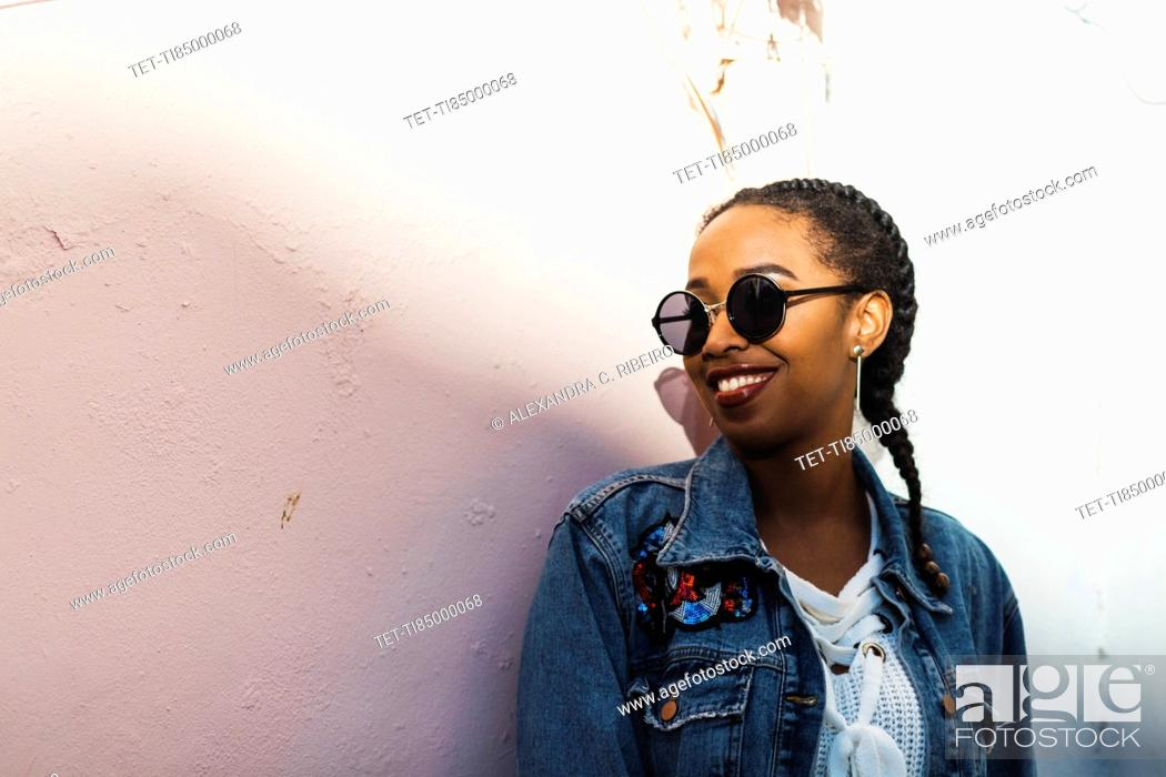 Stock Photo: Smiling young woman wearing sunglasses and denim jacket standing by white wall.