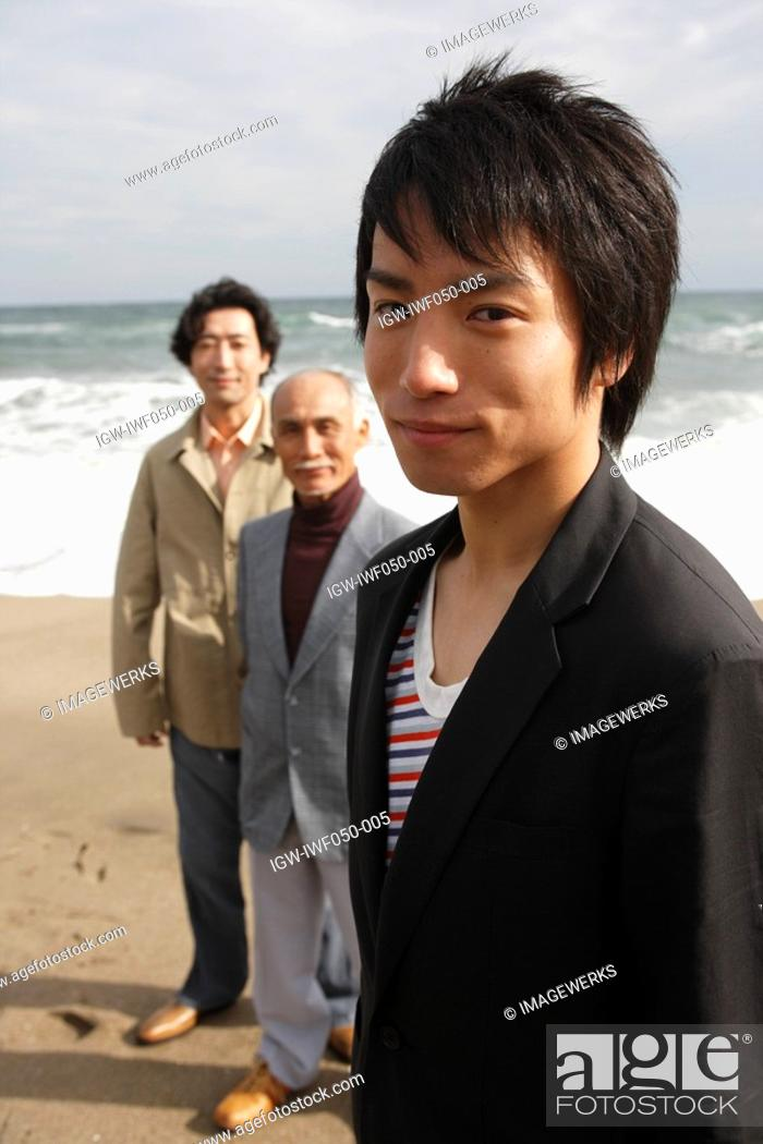 Stock Photo: Young man smiling while grandfather and father standing in background, portrait.