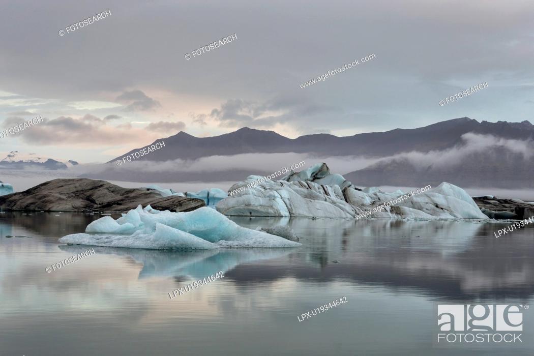 Photo de stock: Icebergs at Jokulsarlon lagoon, with glacier , sunrise, Iceland.