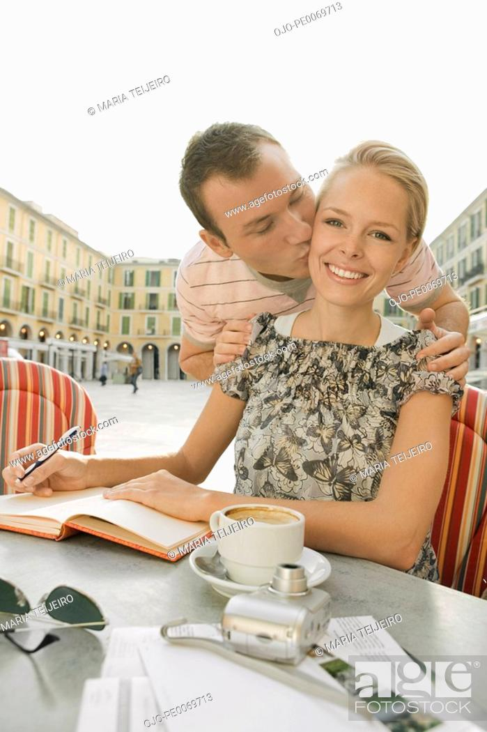 Stock Photo: Man kissing woman sitting at cafe table.