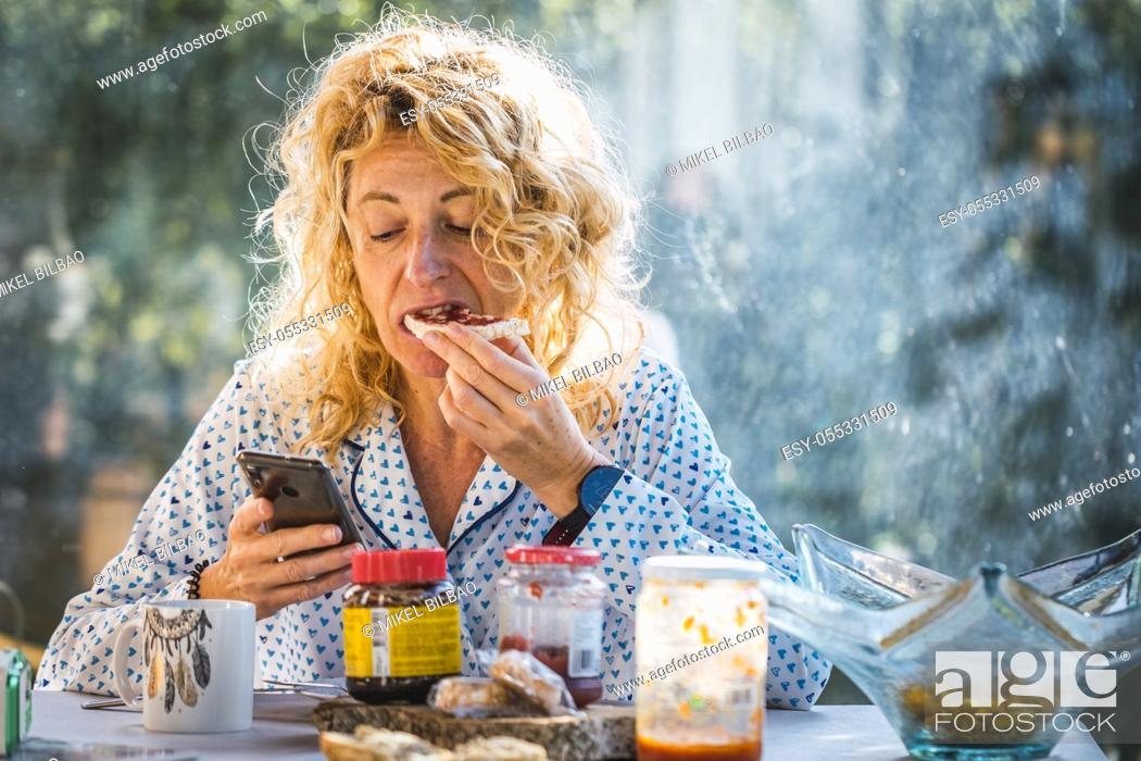 Imagen: Blonde young mature woman in pyjamas at home in breakfast time looking his mobile and eating a toast.
