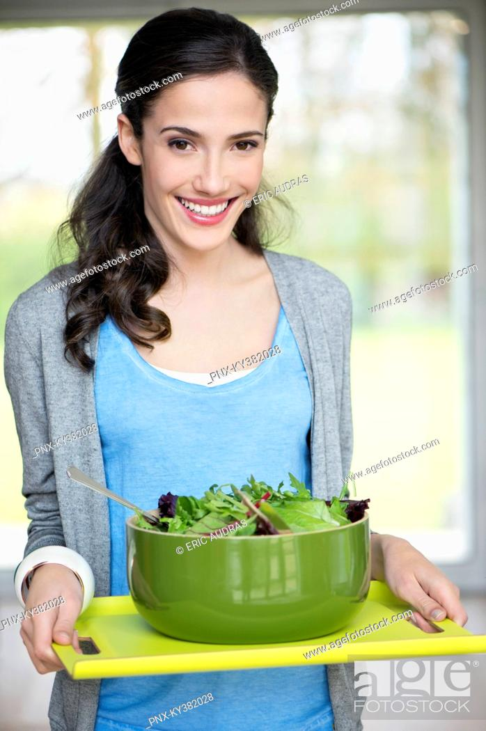 Stock Photo: Woman carrying a bowl of salad on a tray.