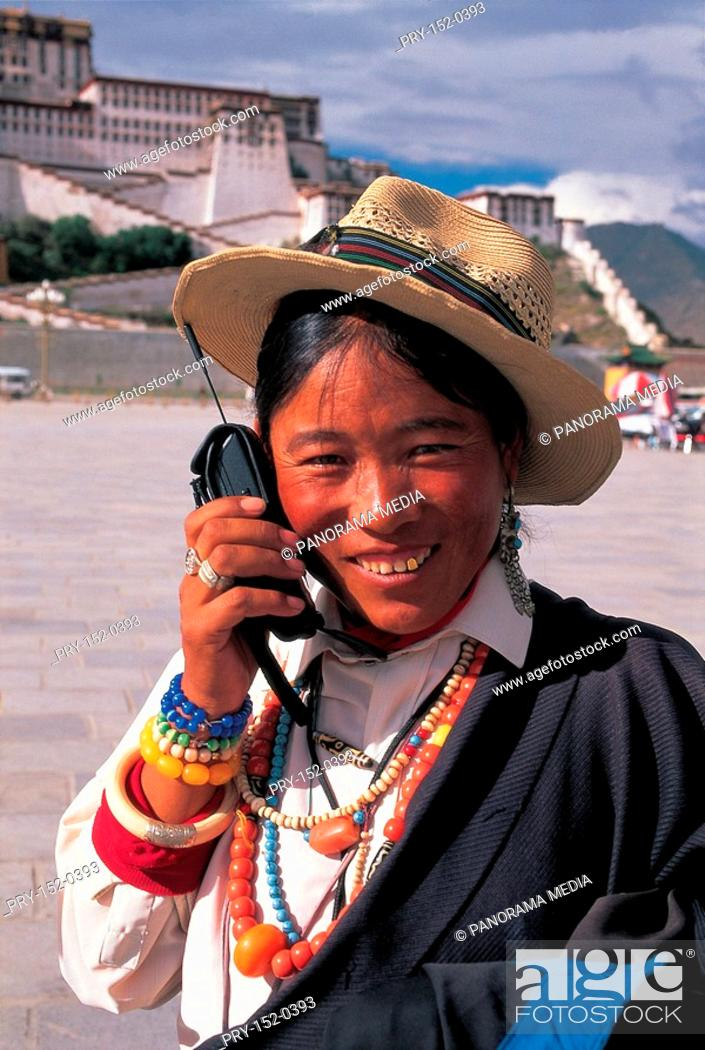 Stock Photo: Tibet woman talking on cellphone in front of Potala Palace.