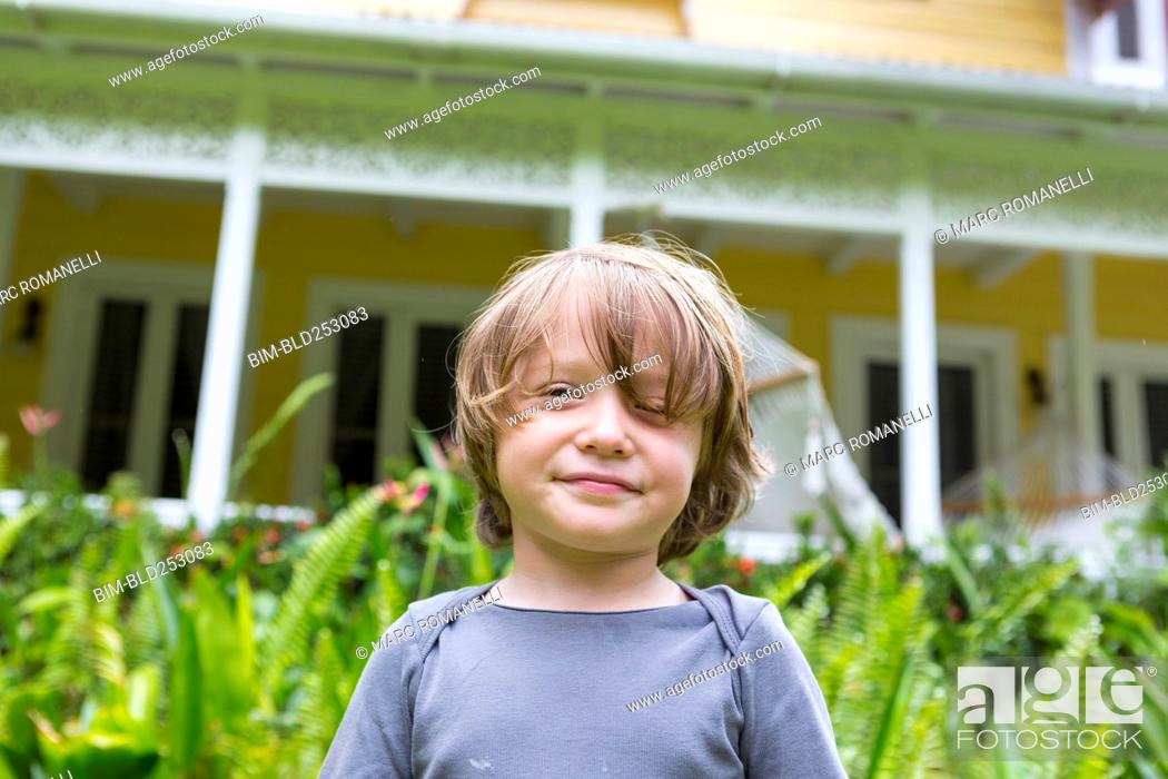 Photo de stock: Smiling Caucasian boy in front of house.