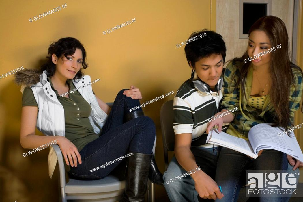 Stock Photo: Young couple reading a book with a young woman sitting beside them.