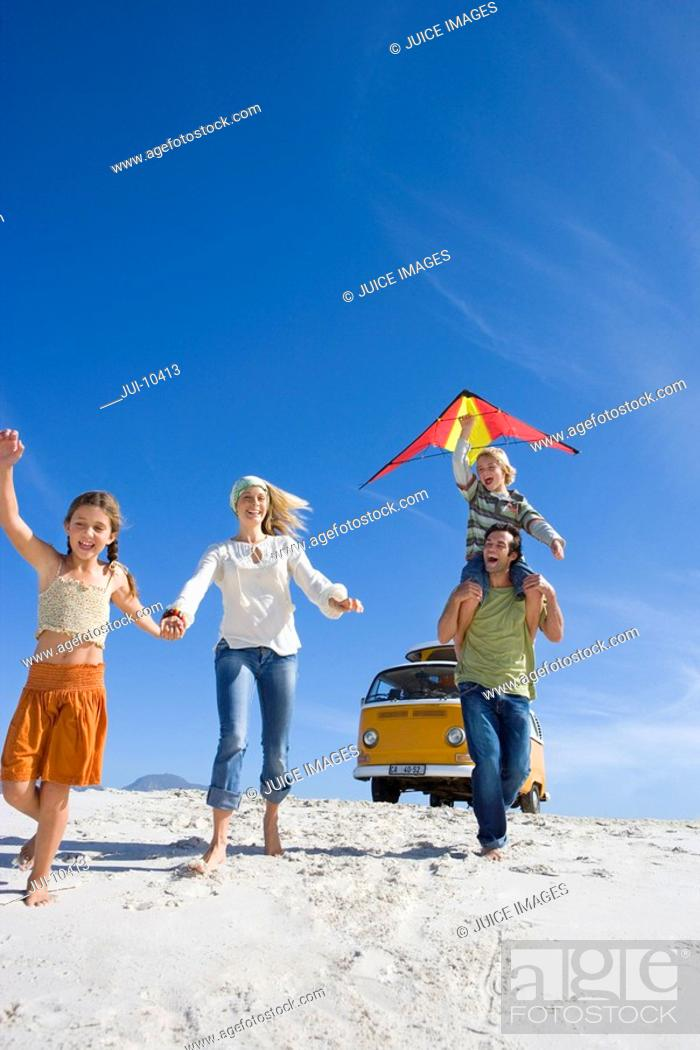 Stock Photo: Family of four on beach, son 6-8 on father's shoulders with kite, low angle view.