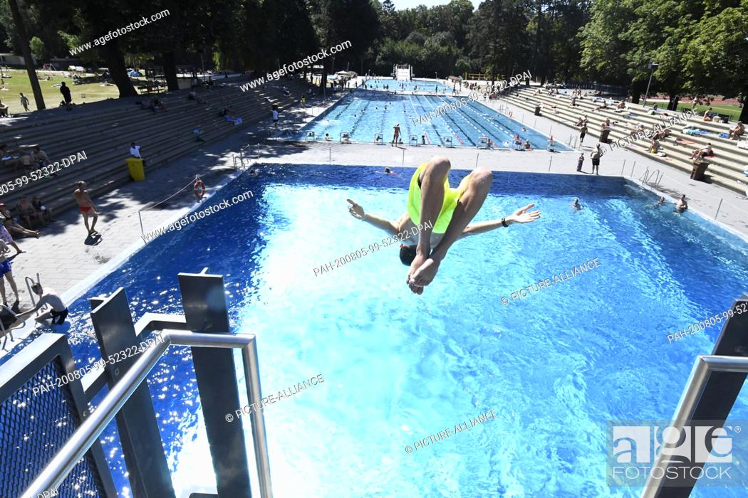 Stock Photo: 05 August 2020, North Rhine-Westphalia, Cologne: A young man uses the diving tower of the stadium pool and cools down. Meteorologists predict a heat wave with.