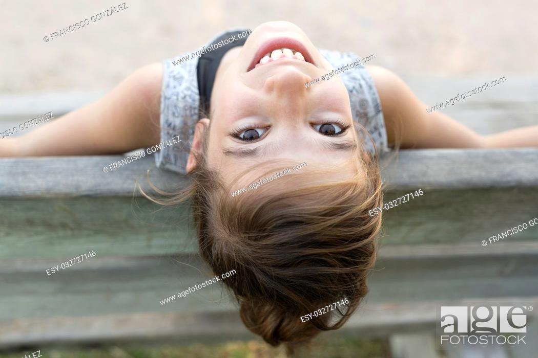 Stock Photo: Young girl turning to take a photo in a park in Alicante.