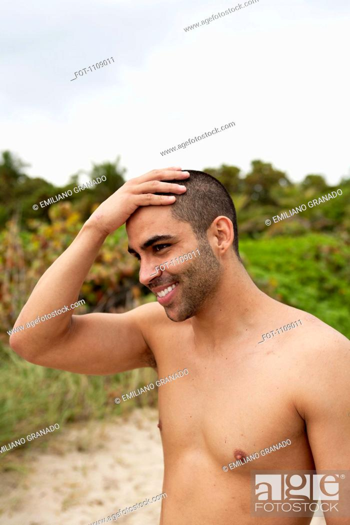 Stock Photo: A cheerful young man rubbing his head at the beach.