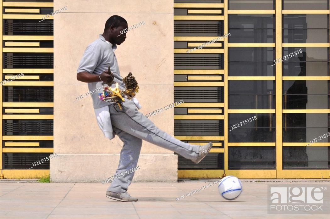 Stock Photo: Paris, France, an African immigrant, souvenirs peddler, playing soccer by the Palais de Chaillot, Trocadero.