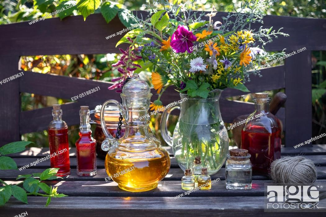 Stock Photo: Bottles of herbal and essential oils with fresh medicinal plants in a garden.