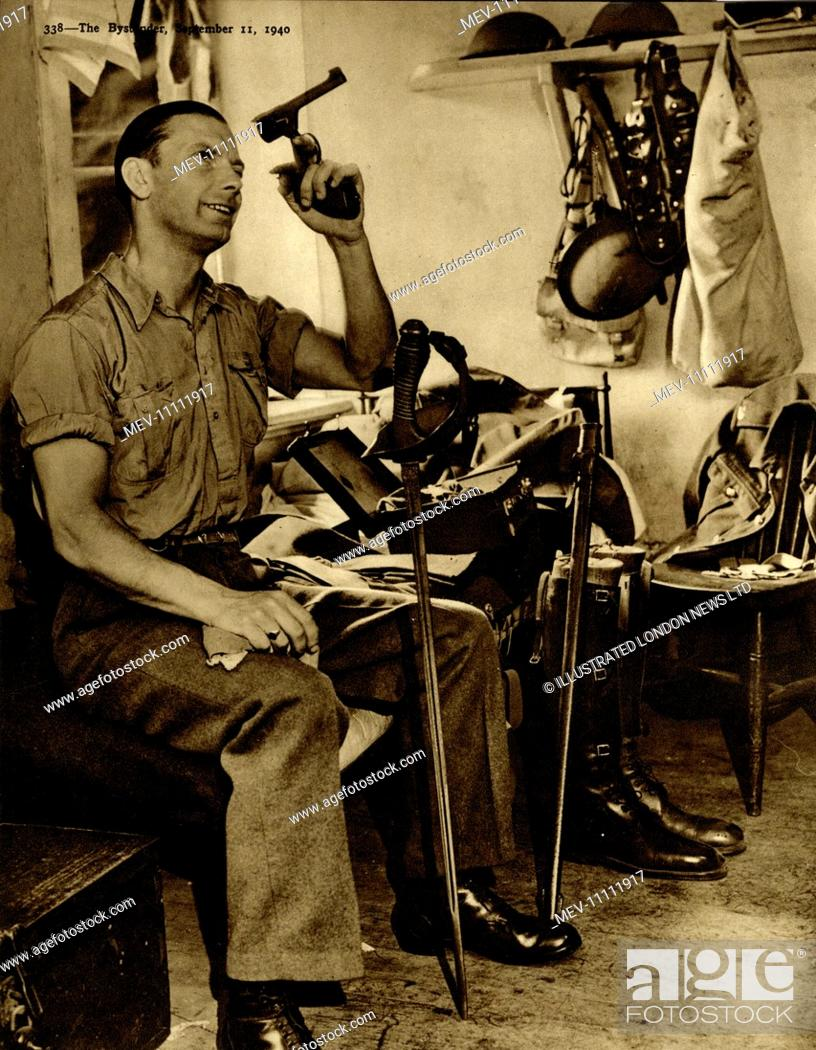 Soldier S W  Saunders cleans out his revolver, with his
